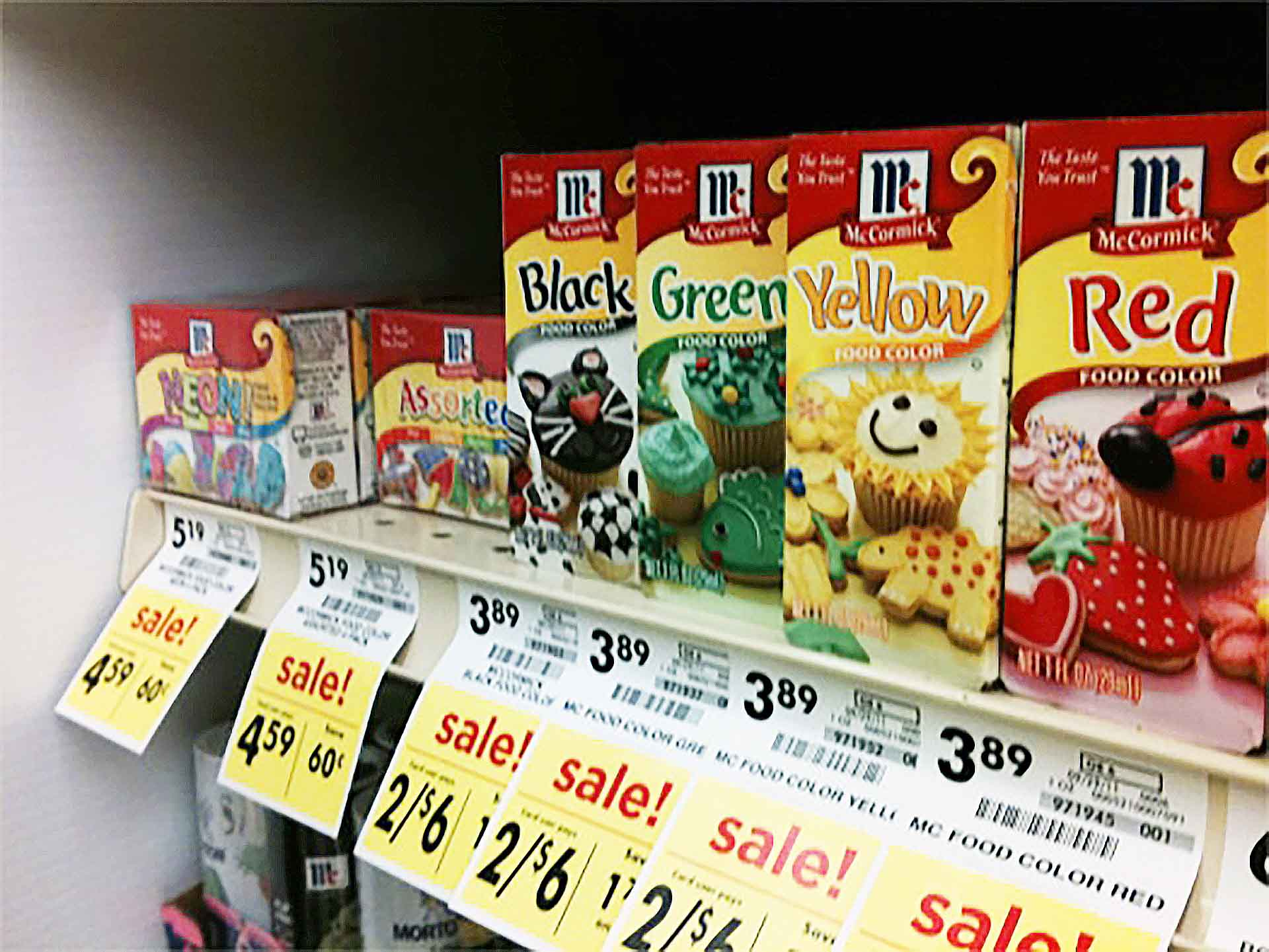 Row of artificial food colors on sale at a grocery store.