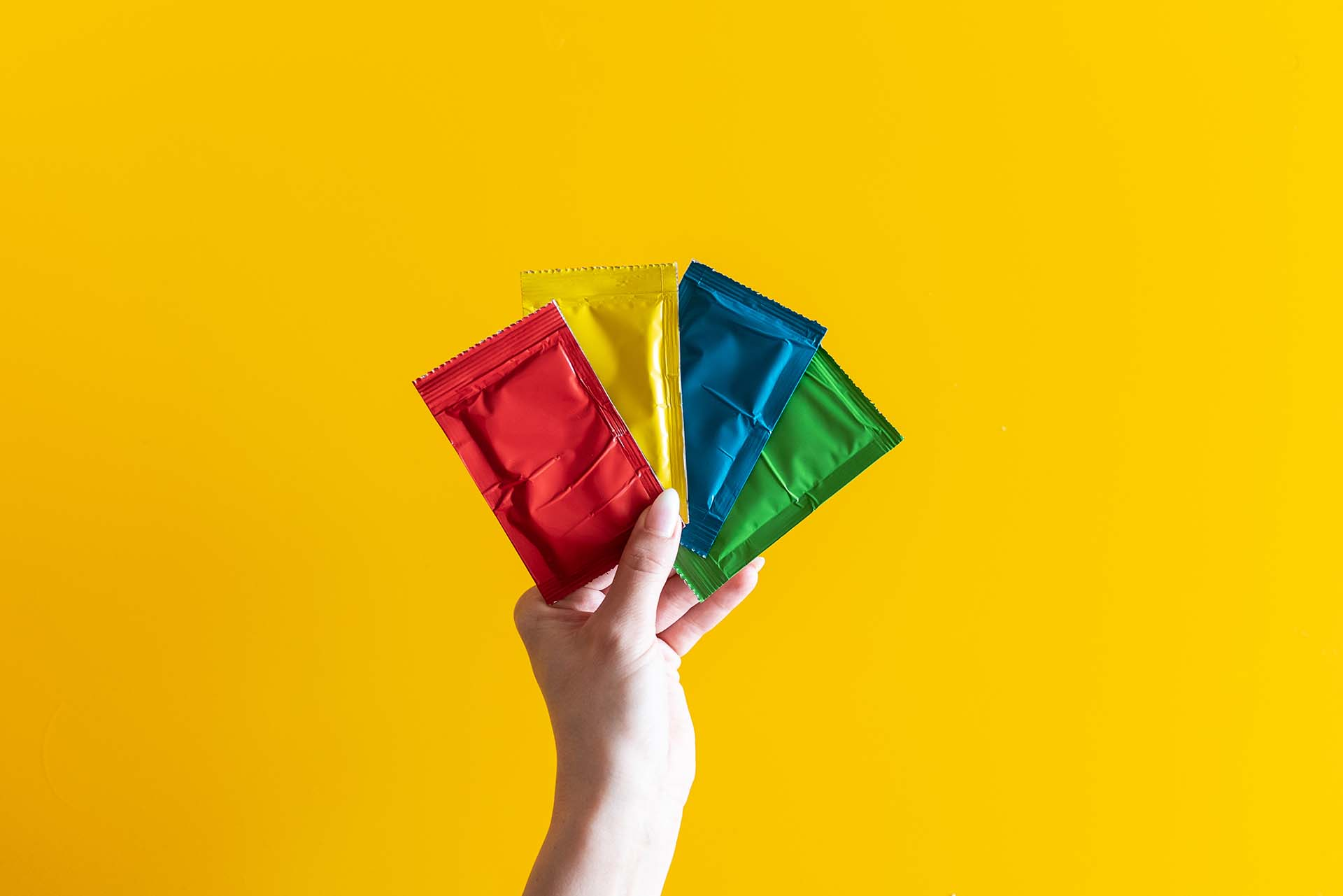 A hand holding four different color pouches of food colors in front of a bright yellow wall.