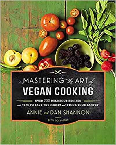 Cover for the book Mastering the Art of Vegan Cooking. Featuring a selection of fruits and vegetables, some cut open in half, some not, on top of a weathered green wooden surface.