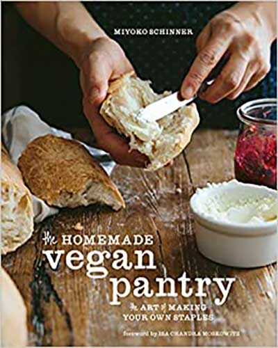 A cover for the book Homemade Vegan Pantry. Features a wooden table with bread and butter on it and a hand buttering a piece of bread.