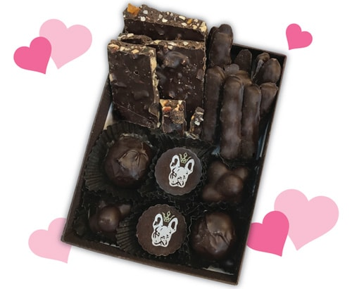 A closeup of an assortment of chocolate candy in a box surrounded by pink hearts.