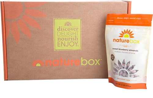 A closeup of a package of snacks sitting next to a cardboard box with the Naturebox logo on it.