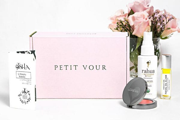A pink Petit Vour box sitting on a white counter with a variety of beauty products around as well as a vase of pink roses.