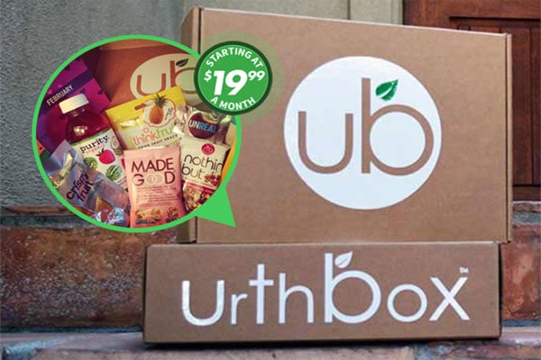 A closeup of a carboard box with the Urthbox logo on it sitting on a brick front steps.