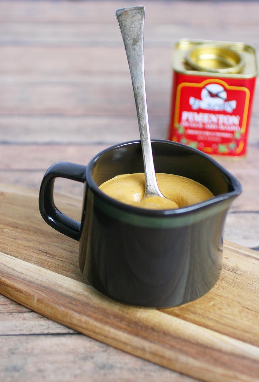 A brown pitcher of cream sauce sitting on a wooden board with a tin of paprika sitting in the background.