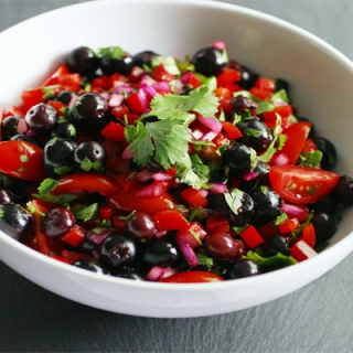 A bowl of blueberry salsa sitting on a table.