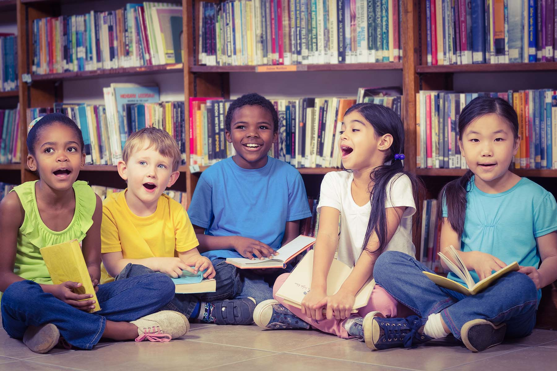 A group of children sitting on the floor of a library