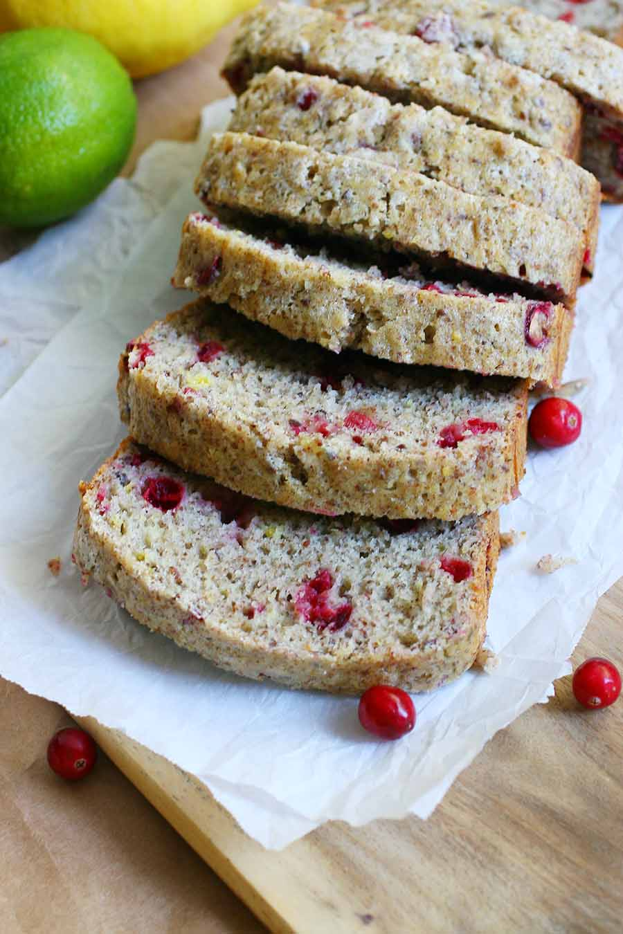A loaf of quick bread sitting on parchment paper on top of a wooden table with lemons, limes, and cranberries strewn about.