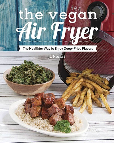 Cover for the book, The Vegan Air Fryer. Features several plates of fried vegan food sitting next to an air fryer on top of a white table with a blue background.