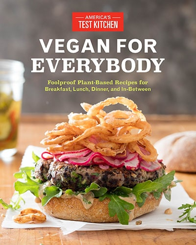 Cover for the book, Vegan For Everybody. Features a picture of a scrumptious-looking vegan burger sitting on a wooden table with a drink in the background.