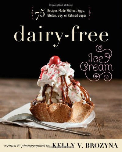 Cover for the book, Dairy-Free Ice Cream. Features a ice cream sundae sitting on a napkin with a spoon nearby and sitting on a wooden tabletop with a black background.