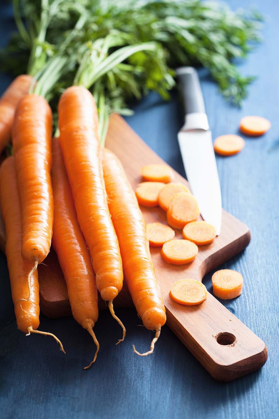 fresh carrot on cutting board with a knife.