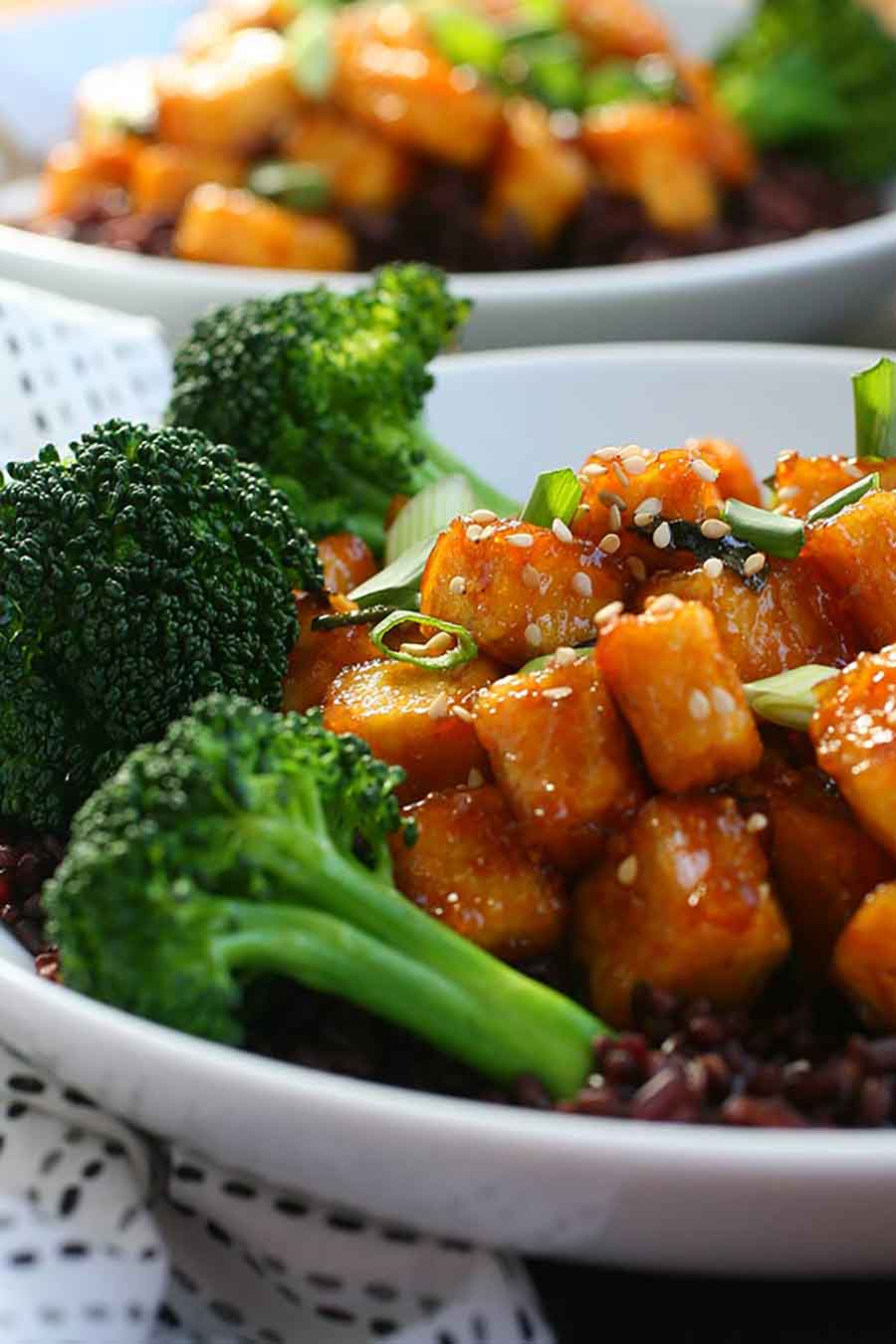 A closeup of two bowls of vegan General Tso's tofu with steamed broccoli.