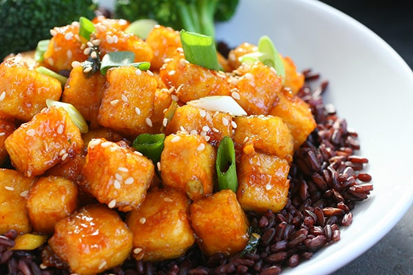 A serving of crispy General Tso's Tofu sitting on top of black rice inside a white bowl.