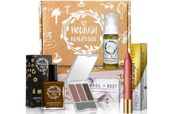 Various beauty products sitting in front of a cardboard box with the Nourish Beauty logo on it.