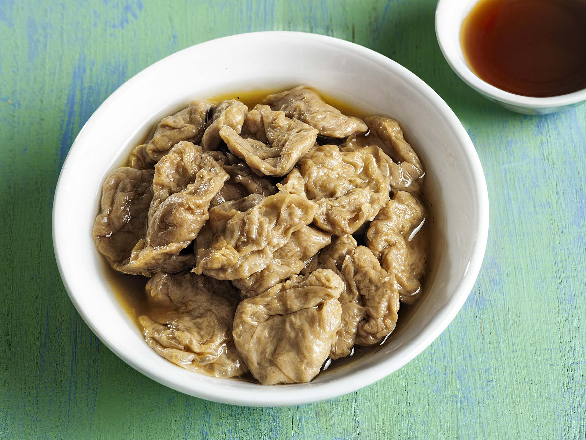 A close up of a bowl of seitan and a side of soy sauce sitting on a blue/green background.