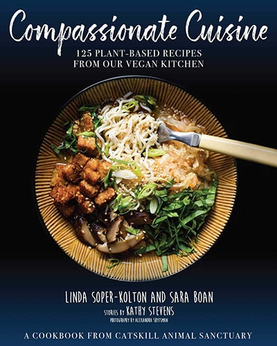 Cover for the book, Compassionate Cuisine. Features an overhead picture showing a bowl of vegan good on a dark background.