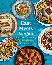 Cover of the book, East Meets Vegan. Features seven different colorful plant-based meals sitting on a blue table.