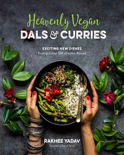 Cover for the book, Heavenly Vegan Dals & Curries. Featuring two hands holding a bowl of colorful vegan food with vegetables surrounding the bowl on a dark background.