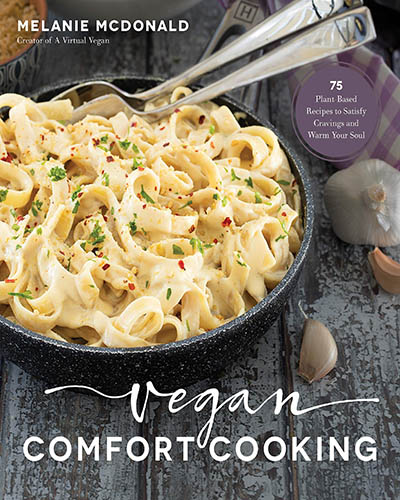 Cover for the book, Vegan Comfort Cooking. Features an iron skillet filled with a creamy pasta dish. The iron skillet is sitting on top of a rustic wooden table with garlic cloves laying about.