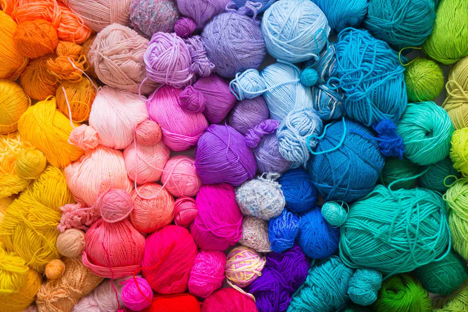Overhead picture of balls of yarn with the colors arranged in a rainbow pattern.