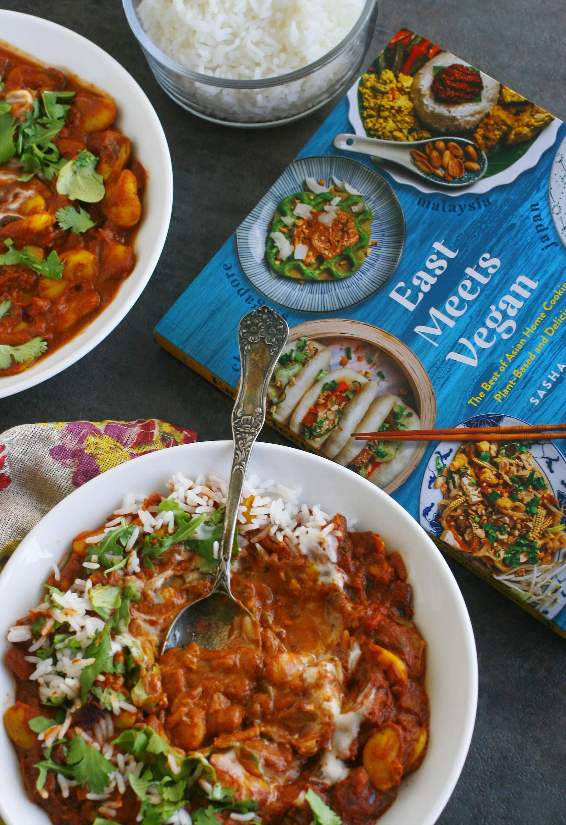 Two white bowls of tikka curry sitting on a table with a copy of the cookbook.