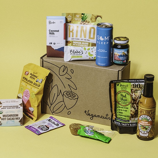 A vegancuts snack box with a variety of snacks displayed on a yellow background.