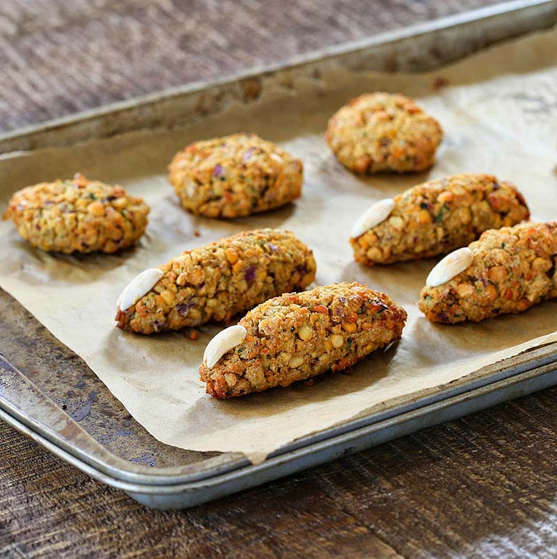 Several baked falafel fingers sitting on a parchment-lined baking sheet.