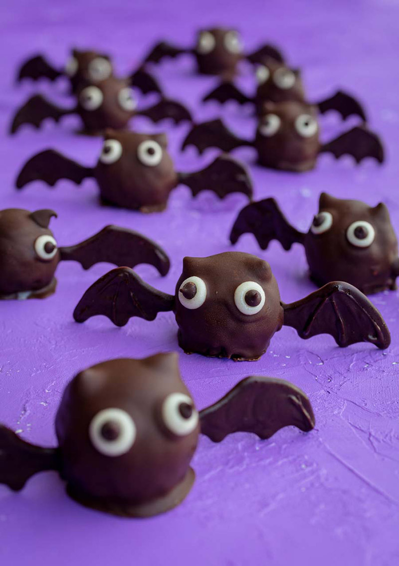 A closeup of a eight bat truffles sitting on a purple tabletop.