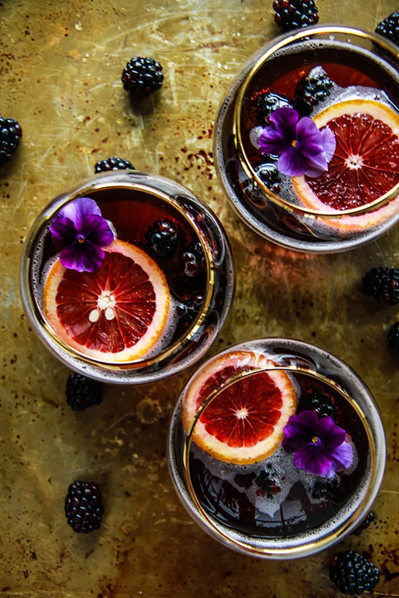 An overhead view of three glasses of a red cocktail with floating slices of blood orange and small purple flowers sitting on top of a dark textured background.