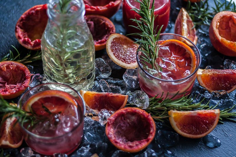 An overhead of halved blood oranges and glasses of red cocktails sitting on a black background.