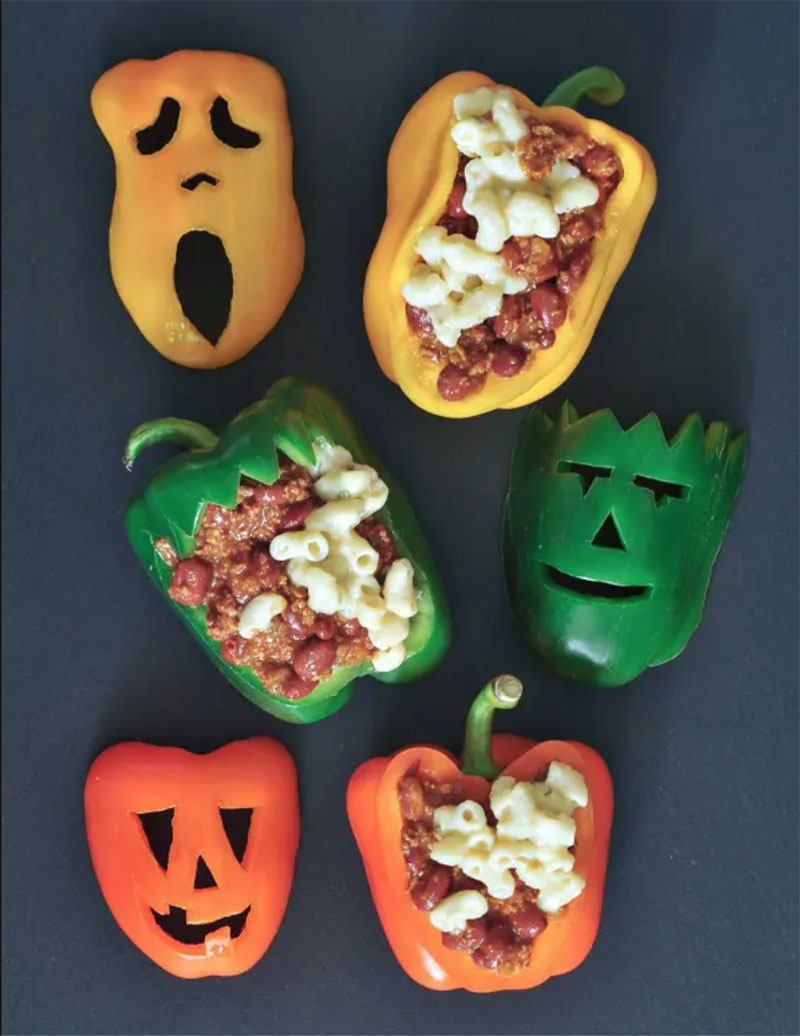 Three stuffed peppers (one green, one orange, one yellow) cut into jack-o-lanterns sitting on a black background.
