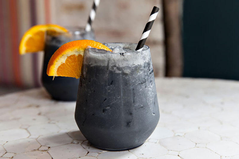 Two clear glasses with a dark frozen drink with an orange slice garnish and a black and white straw sitting on top of a white counter.