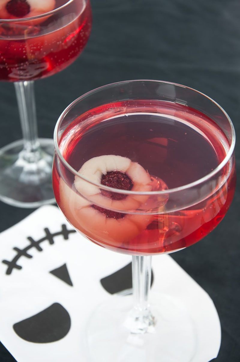 Two glasses of a red cocktail with a floating fruit eyeball sitting on a white skull placemat.