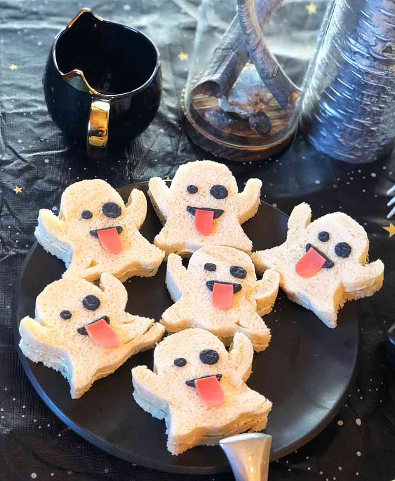 A plate of tea sandwiches that are cut into ghost shapes sitting on a plate.