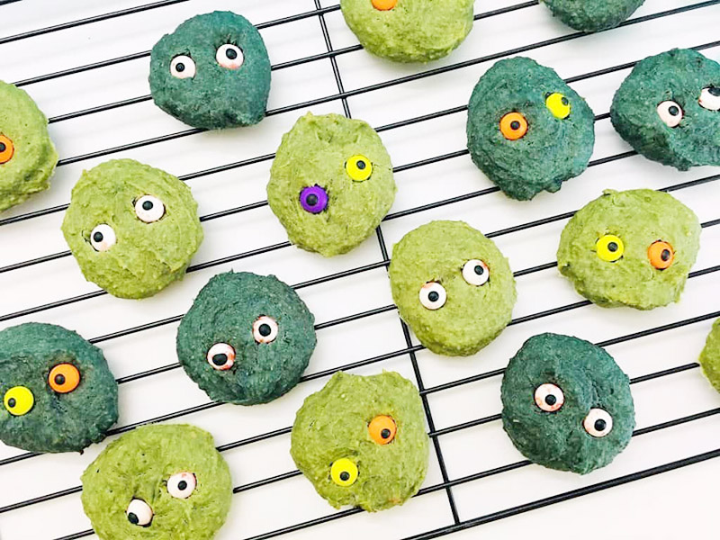 Rows of light green and dark green cookies with google eyes sitting on a baking rack with a white background.
