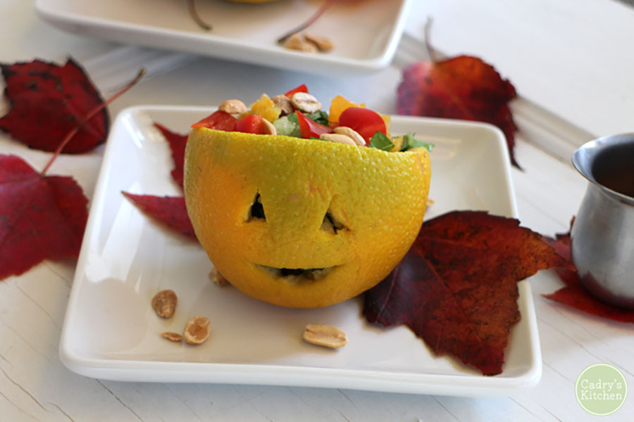 An orange jack-o-lantern bowl sitting on a white plate with fall leaves scattered about.