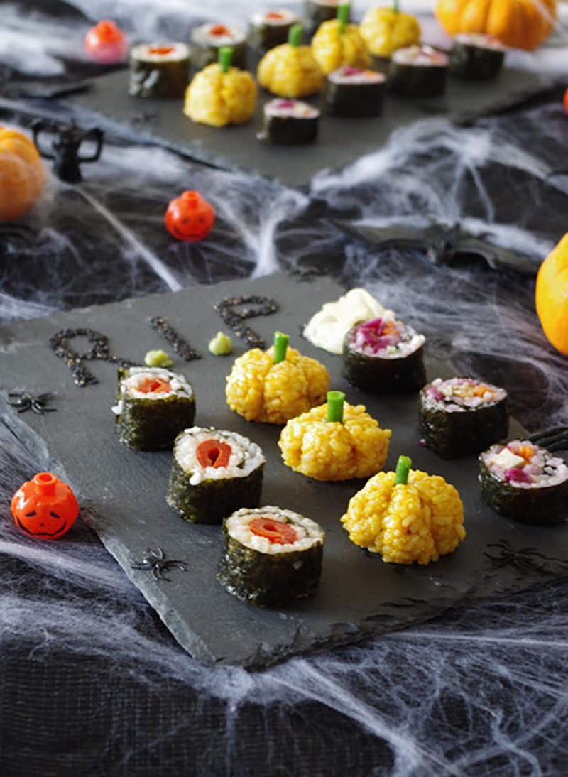 Two slate platters filled with Halloween-shaped sushi pieces with spooky spiderwebs in the background.