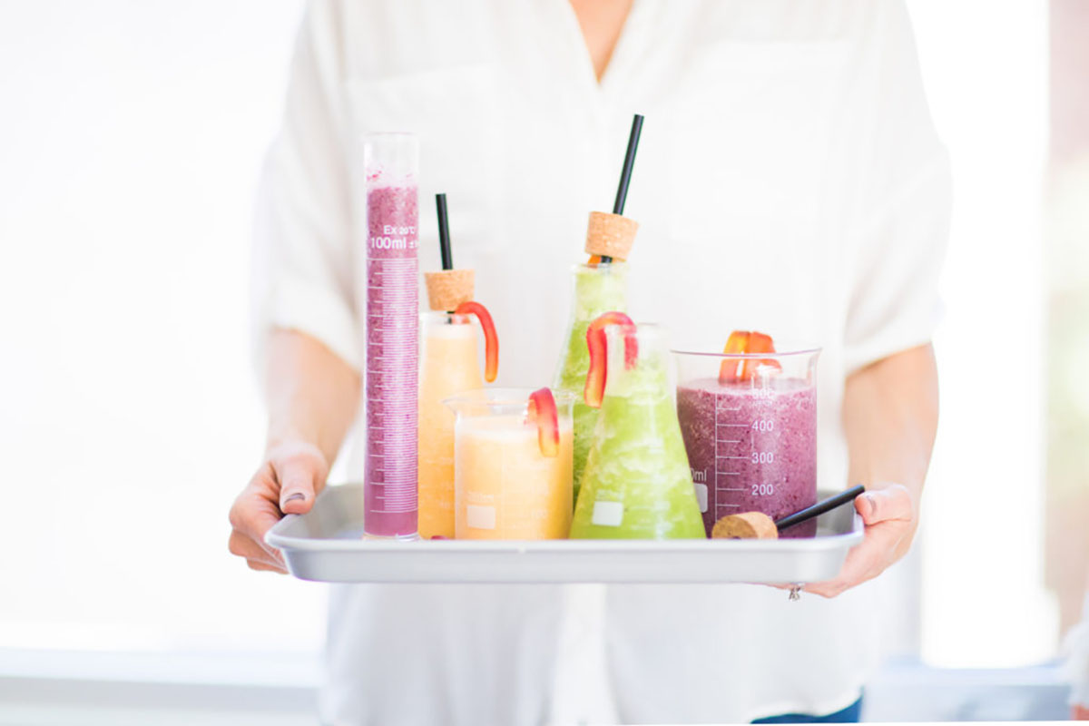 A closeup of a woman wearing a white shirt from neck to waist holding a tray of brightly colored smoothies.