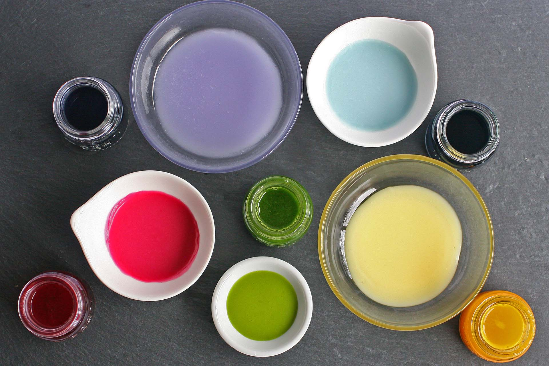 A variety of bowls and jars with various homemade food dyes in them (red, green, yellow, blue, purple).