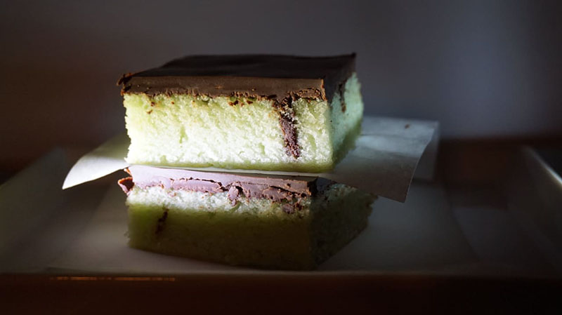 A closeup of two pieces of cake stacked one on top of another.