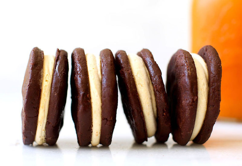 A closeup of four pumpkin spice oreos with a white background.