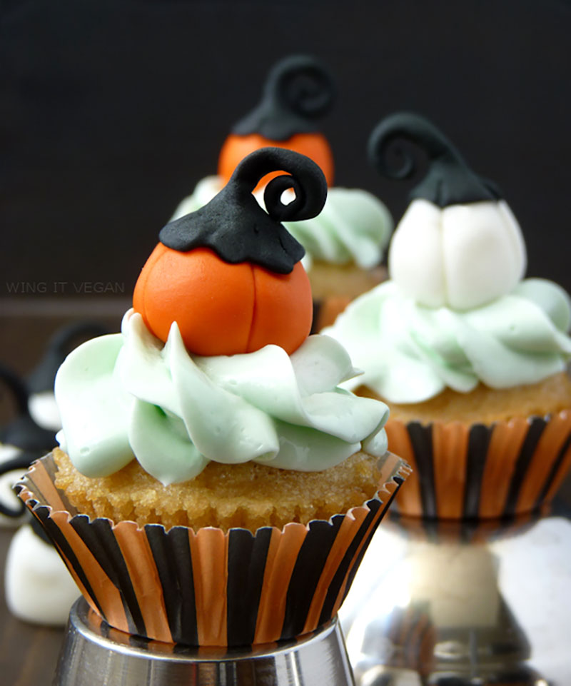 A close of of vanilla cupcakes with mint green frosting and decorative pumpkins on top sitting inside black and orange striped wrappers.