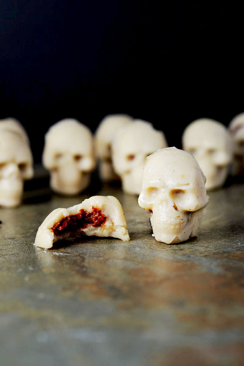 A closeup of rows of white chocolate skulls with one in front that has been bitten into revealing a red inside.