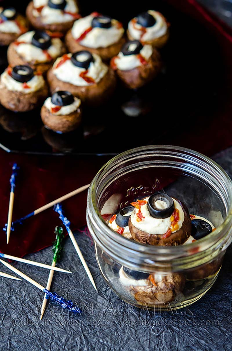 A jar of stuffed mushrooms that look like eyeballs in a jar sitting next to a platter of the same mushroom eyeballs.