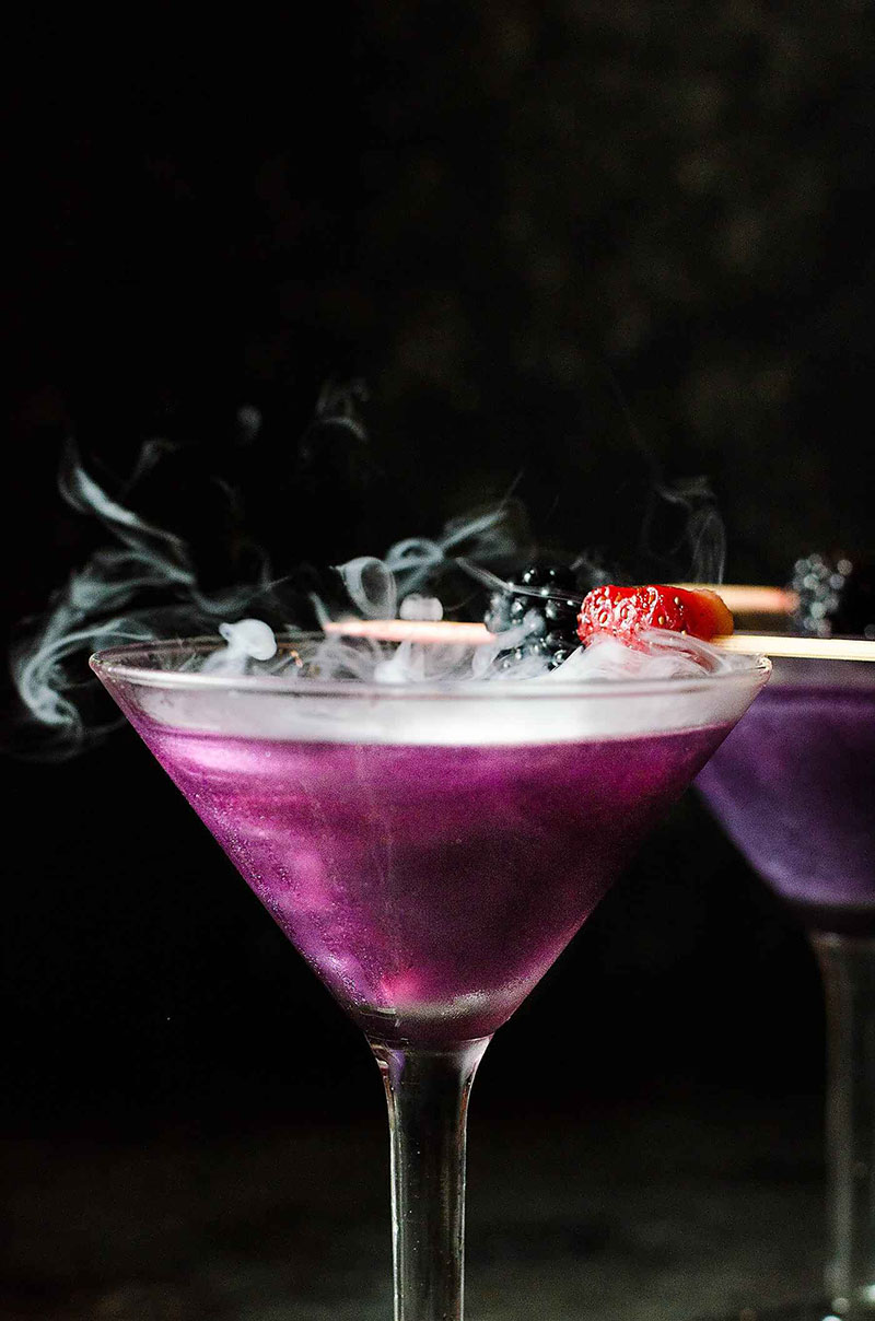 Two smoking purple drinks served in martini glasses with a black background.