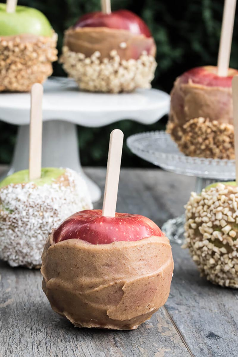An array of caramel apples with different toppings sitting on an assortment of cake stands sitting on a wooden table.