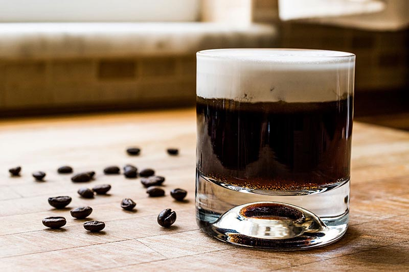 A vegan white russian in a clear glass sitting on a wooden counter with a few coffee beans strewn about.