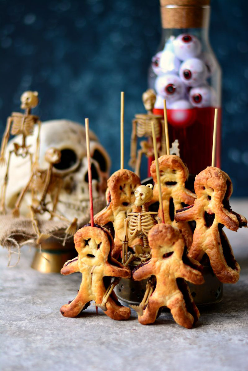 Several VooDoo pastry dolls propped up on a counter with a skull and jar of eyeballs in the background.