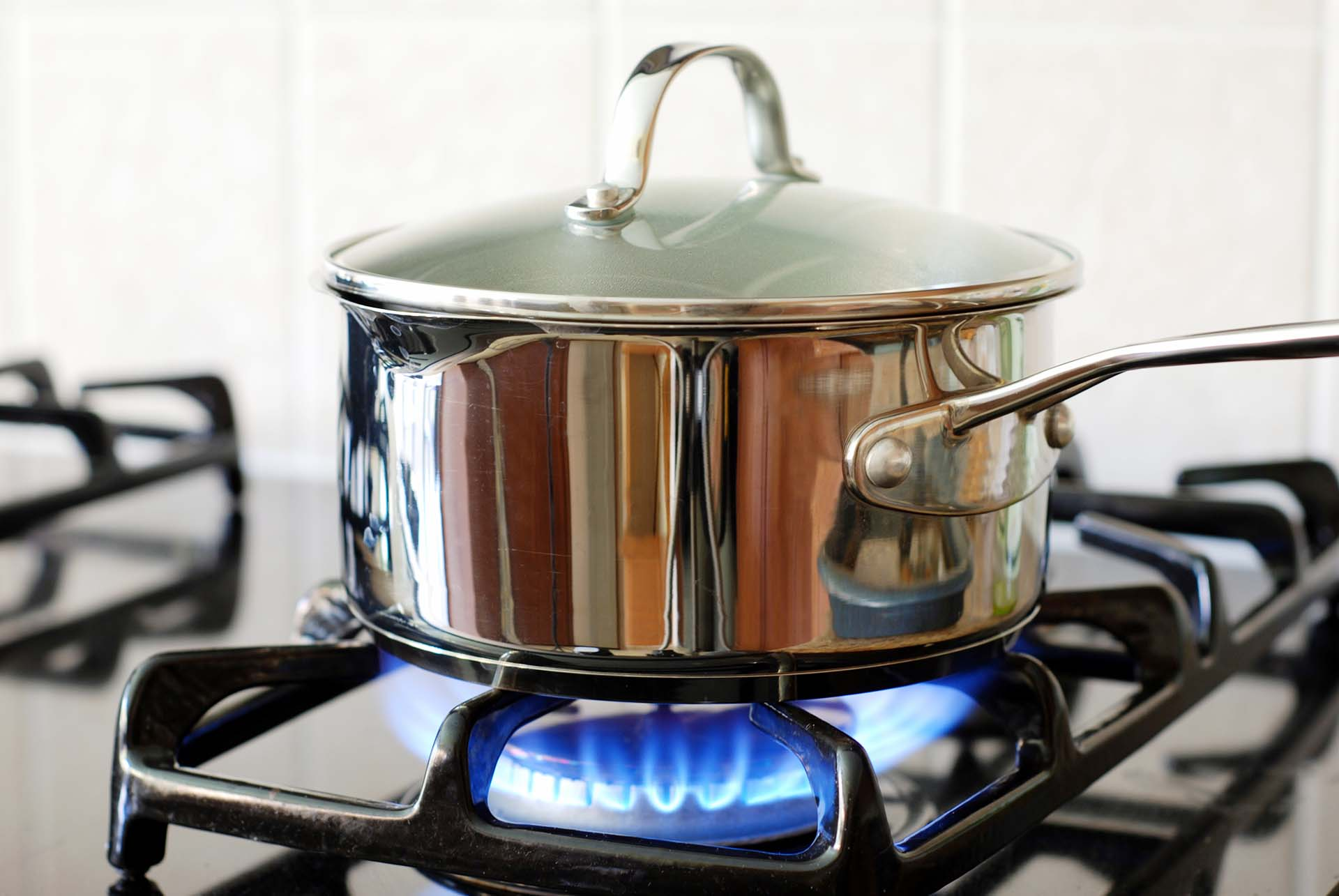 A covered stainless steel pot on a gas burner that is on.